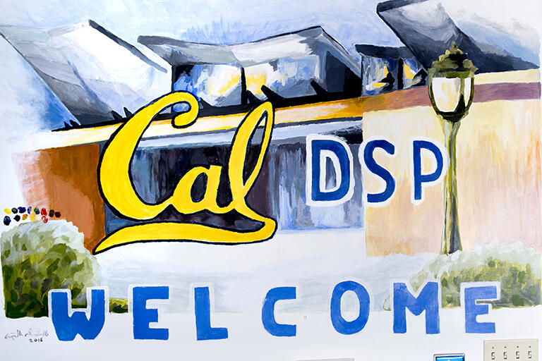 """A mural painted on a wall at DSP. The mural reads """"Cal DSP, Welcome"""" and has a painting of the Cesar Chavez Building in its background."""