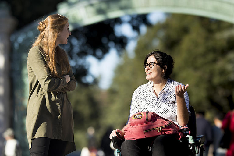 Two students talking in front of Sather Gate. One of the students is a wheelchair user.