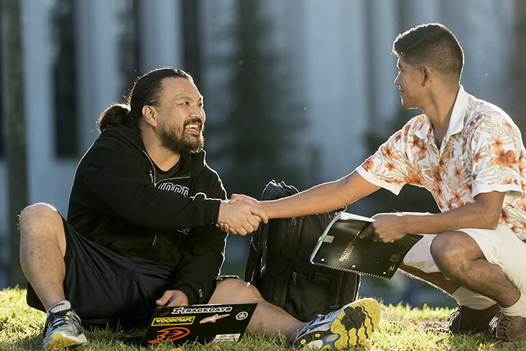 Two students sitting on the grass in front of the Valley Life Sciences Building. They are laughing and shaking hands.