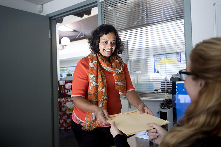 An instructor handing a stack of proctoring envelopes to a staff member.