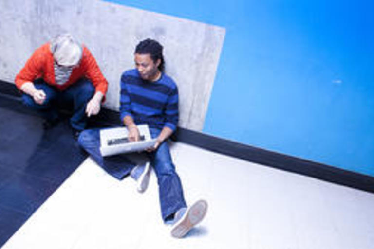 A faculty helping a student with an assignment on their computer.