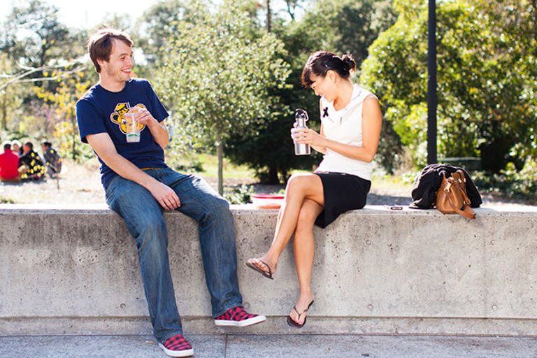 Two individuals sitting on a concrete bench, eating lunch together.