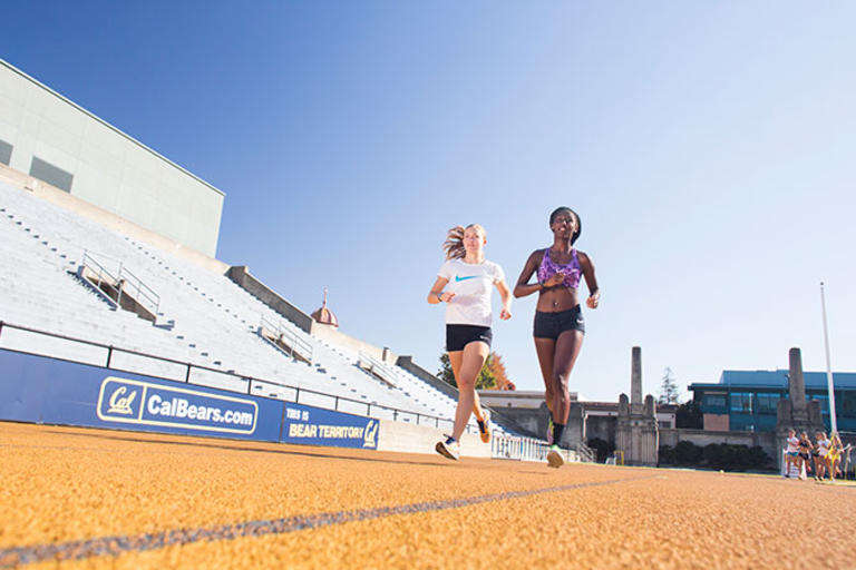 Two students running side by side on a track, with a set of bleachers in the background.