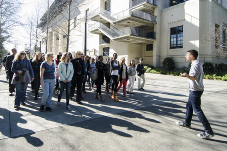 A group of visitors touring the campus, with a tour guide leading them.