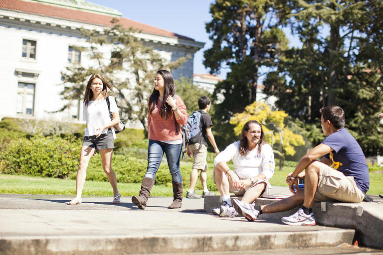 A group of students in front of California Hall- some are sitting on the floor relaxing, others are walking together.