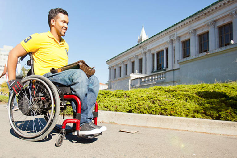 A student in a manual wheelchair strolling in front of Doe Library