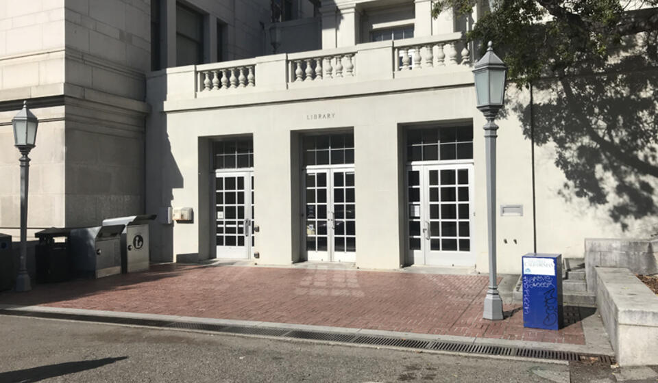 The south accessible entrance to Bancroft Library. To the right of the leftmost set of doors is an automatic door opener.