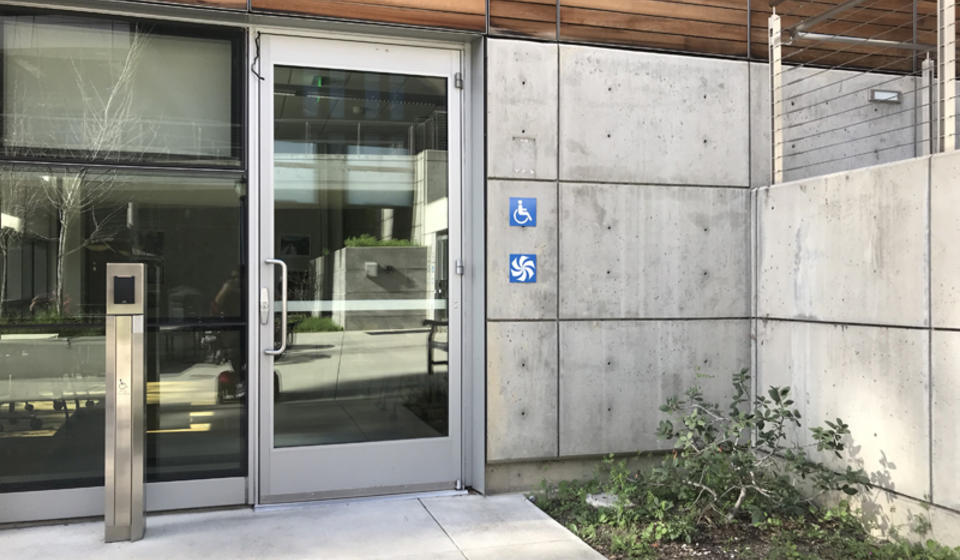 The accessible entrance to Blum Hall, facing east. To the left of the double doors is an automatic door opener.