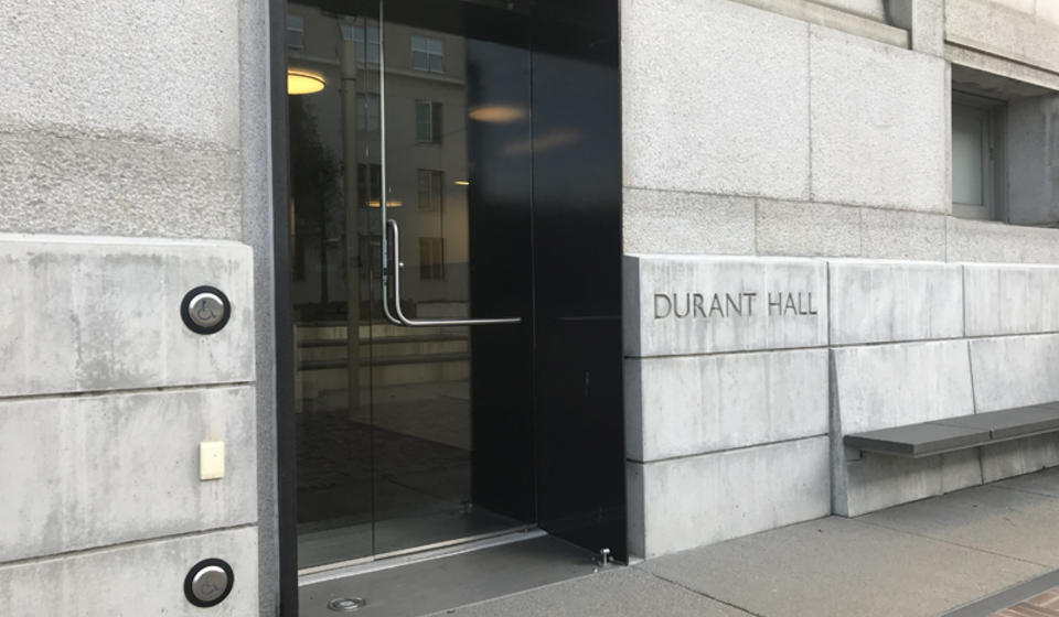 The west entrance to Durant Hall. To the left of the entrance is an automatic door opener.