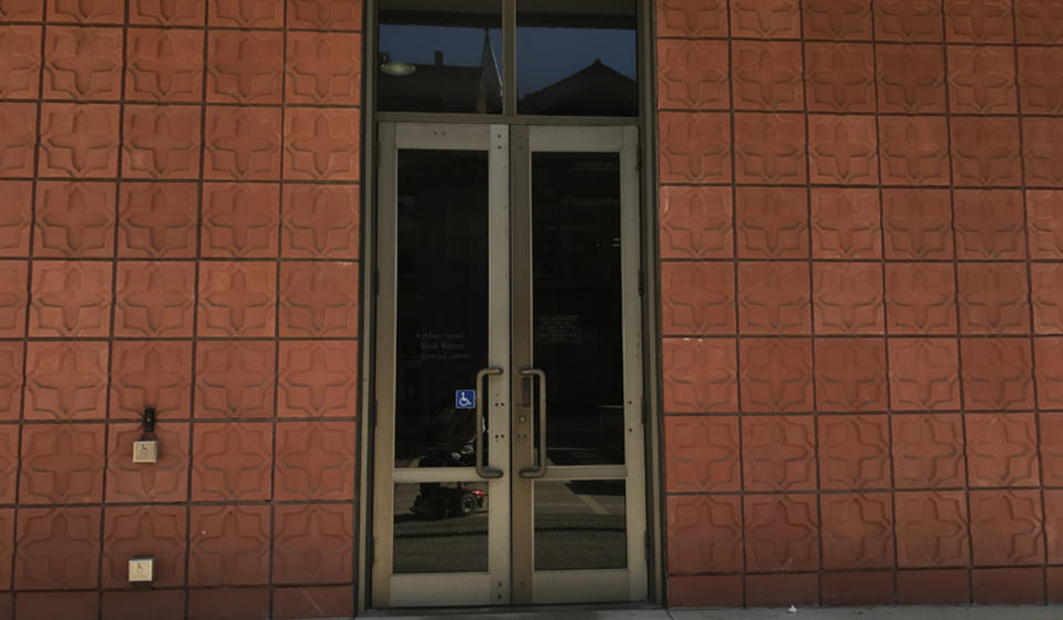 The upper entrance to Hildebrand Hall. To the left of the doors is an automatic door opener.