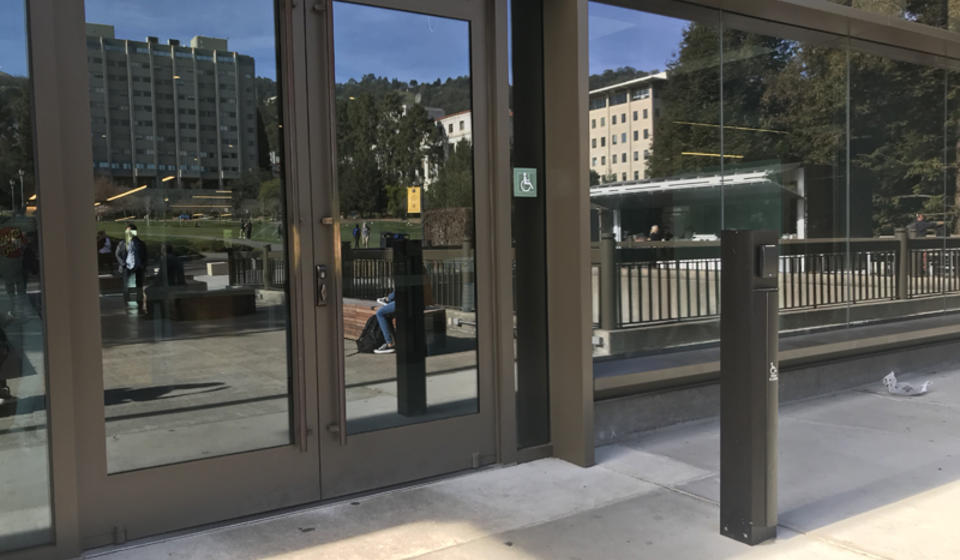 The upper accessible entrance to Moffitt Library, on the east side. To the right of the entrance is an automatic door opener