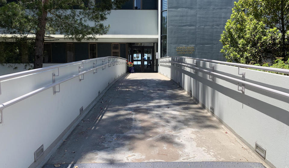 The main entrance to the Silver building, facing East. A bridge from the parking lot leads to the double doors.