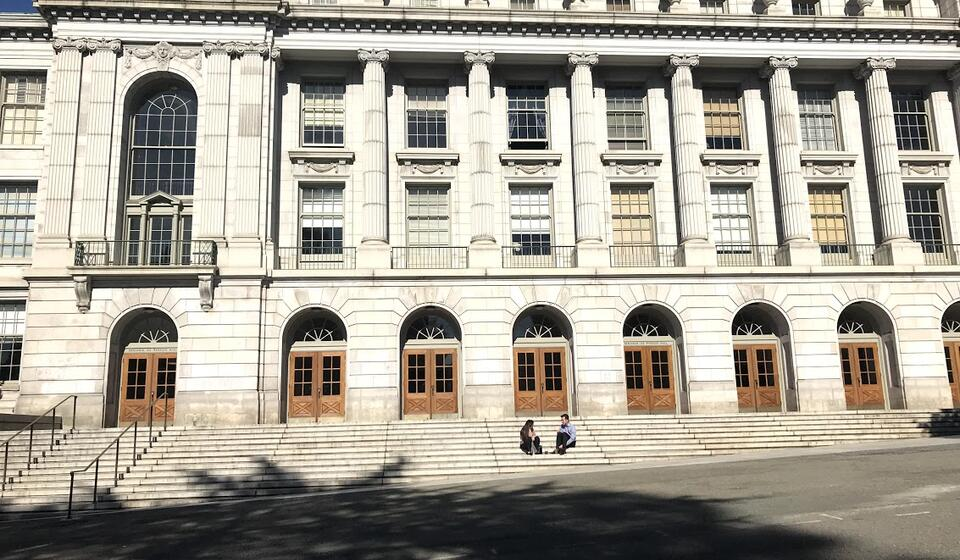 The front side of Wheeler hall, with two students sitting on the front steps